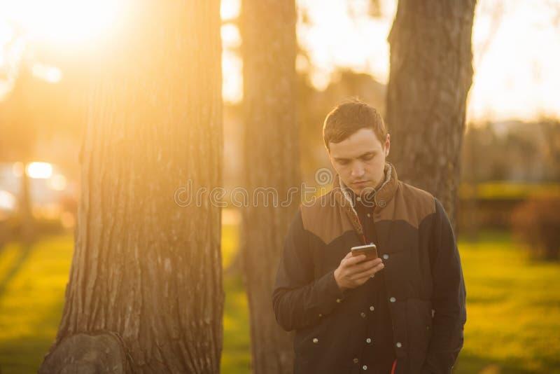 Uomo in parco facendo uso di un telefono Uomo bello immagini stock libere da diritti