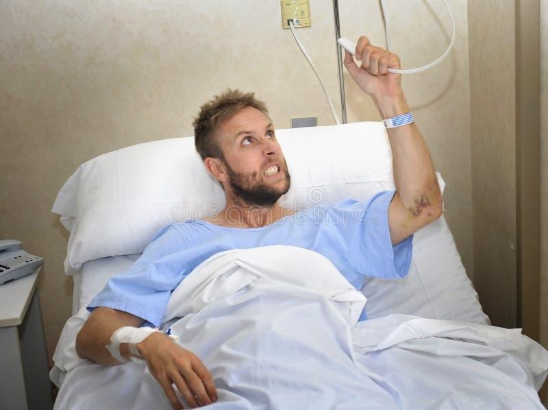 Uomo paziente arrabbiato alla stanza di ospedale che si trova a letto premendo sensibilità del pulsante di chiamata dell'infermie fotografia stock