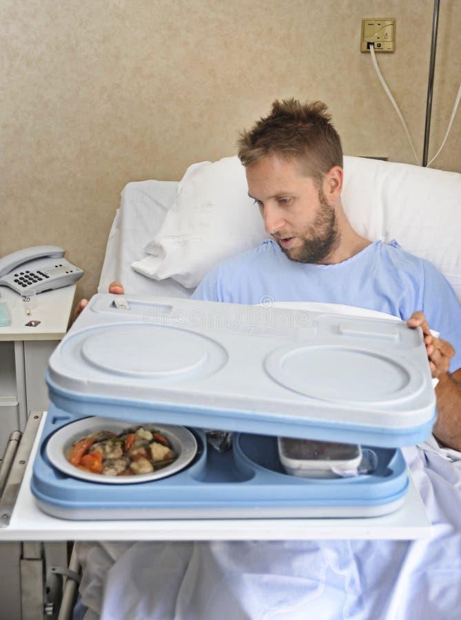 Uomo paziente nella stanza di ospedale dopo che il vassoio di sofferenza del pasto di apertura di incidente pronto ad avere una c fotografia stock libera da diritti
