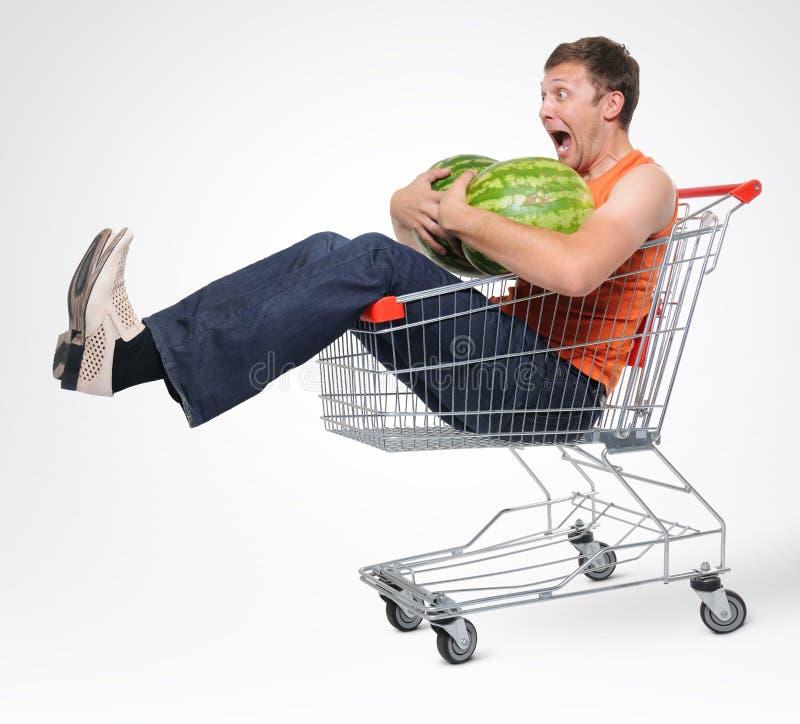 Uomo pazzesco in acquisto-carrello con l'anguria due fotografie stock