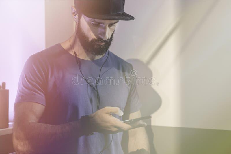 Uomo pensieroso barbuto che indossa il cappuccio nero di snapback che sta sul caffè con le cuffie Uomini che per mezzo del telefo immagine stock