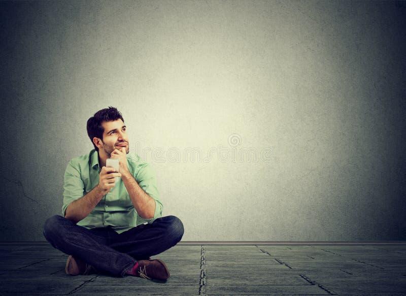 Uomo pensieroso che si siede nel pavimento con il telefono fotografie stock libere da diritti