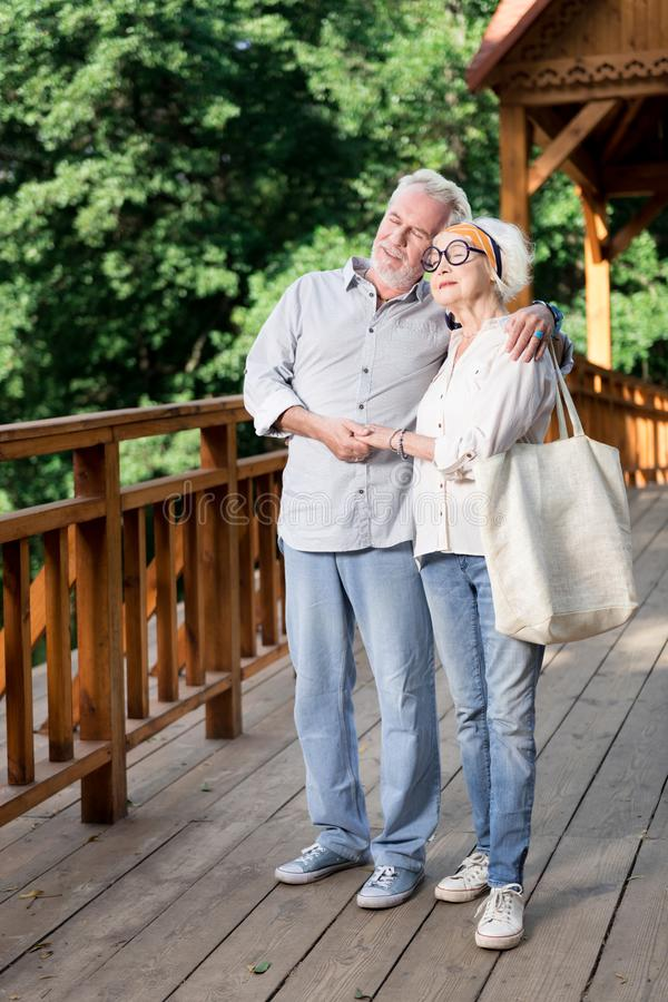 Uomo pensionato barbuto che ritiene adorabile abbracciando la sua bella moglie fotografia stock