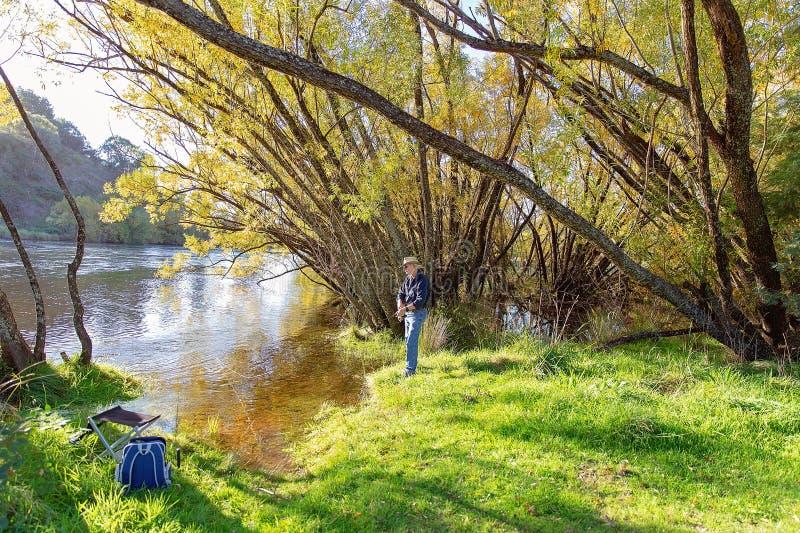 Uomo pensionato che gode della pesca nel paese bello immagine stock libera da diritti
