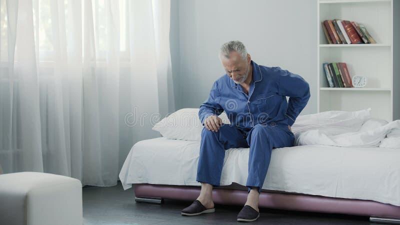 Uomo pensionato che si siedono a letto e parte posteriore, salute e malattia terribili ritenenti di dolore dentro immagine stock