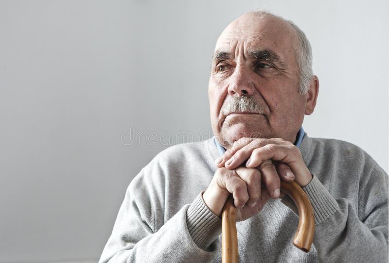 Uomo pensionato dai capelli grigio anziano con il bastone da passeggio immagini stock