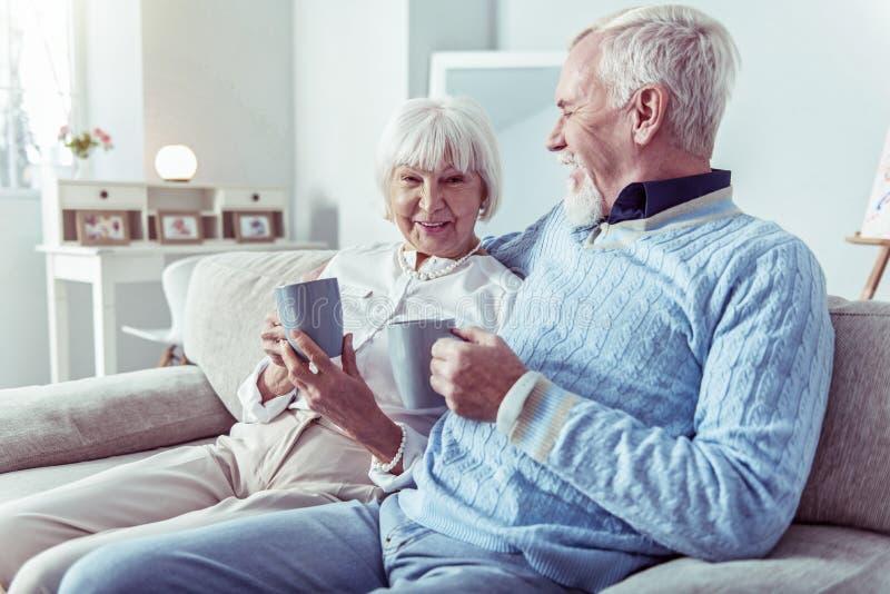 Uomo pensionato di amore preoccupantesi che abbraccia la sua moglie elegante sveglia che si siede sul sofà fotografie stock
