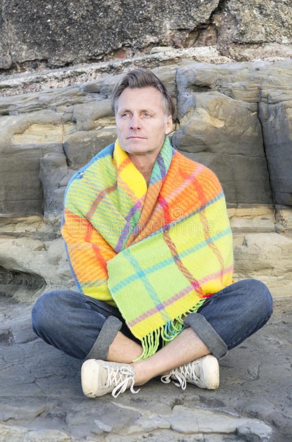 Uomo Pensive che si siede su una roccia da solo. fotografia stock libera da diritti