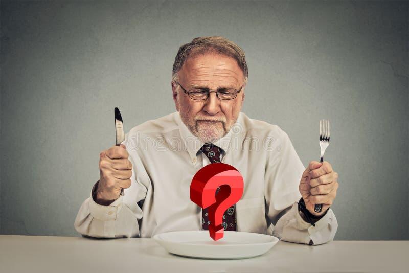 Uomo perplesso senior che sceglie pasto immagini stock