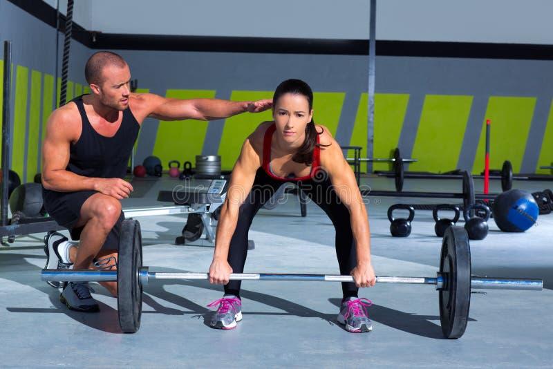 Uomo personale dell'istruttore della palestra con la donna della barra di sollevamento di peso immagini stock libere da diritti