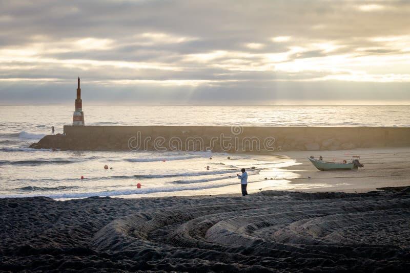 Uomo, pescatore e barca vicino al segnale all'oceano immagine stock libera da diritti