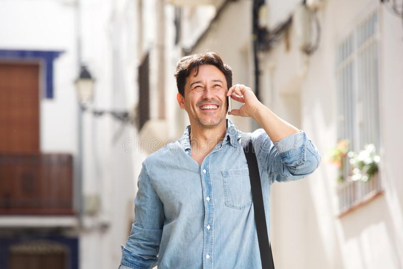 Uomo più anziano allegro che cammina all'aperto e che fa una telefonata immagini stock libere da diritti