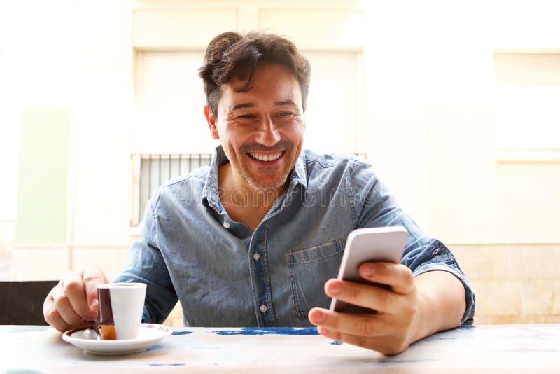 Uomo più anziano allegro con lo Smart Phone e la tazza di caffè immagini stock libere da diritti