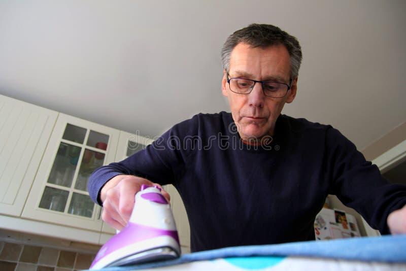 Uomo più anziano che impara come rivestire di ferro i vestiti immagini stock