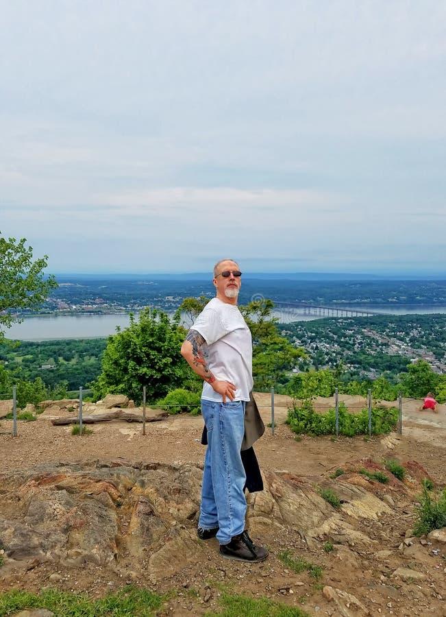 Uomo più anziano che posa sopra una collina, con Hudson River dietro fotografie stock