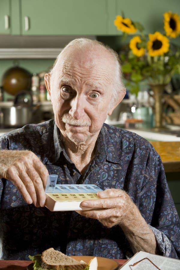 Uomo più anziano con una cassa della pillola immagine stock