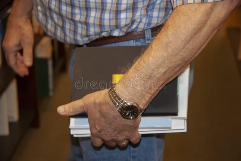 Uomo più anziano potato in jeans e una camicia di plaid che tiene i libri per acquistare in una libreria - fuoco selettivo immagini stock