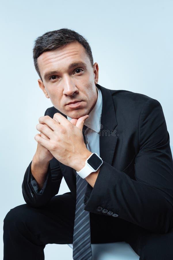 Uomo piacevole piacevole che si siede contro il fondo blu immagine stock