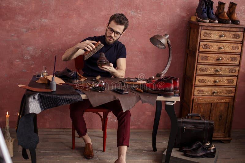 Uomo piacevole di lucidatura delle scarpe che lucida calzature eleganti fotografia stock