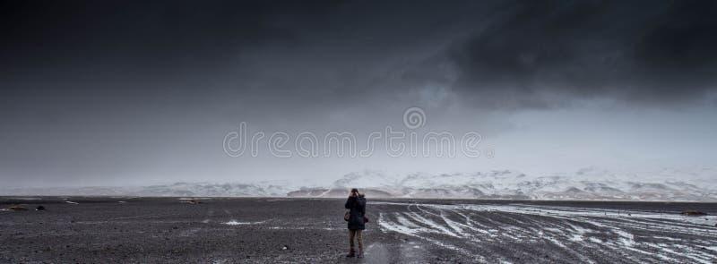 Uomo in piedi su Gray Dessert sotto Grey Cloudy Sky durante il giorno fotografia stock