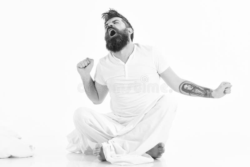 Uomo pieno di energia nella mattina, fondo bianco L'uomo con il fronte sonnolento e di sbadiglio che allunga, sveglia fotografie stock