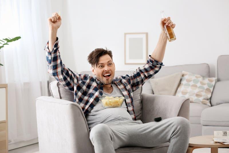 Uomo pigro con la bottiglia di birra e delle patatine fritte che guarda TV immagine stock libera da diritti
