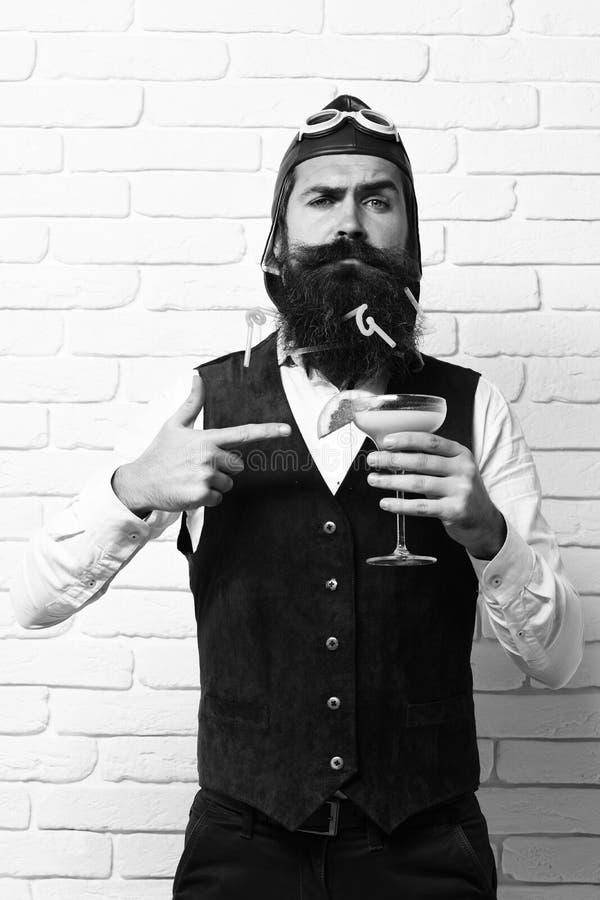 Uomo pilota barbuto bello con la barba lunga e baffi sul fronte serio che tiene vetro del cocktail alcolico in annata fotografia stock