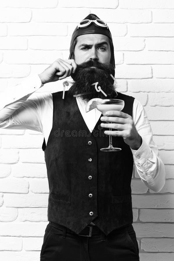 Uomo pilota barbuto bello con la barba lunga e baffi sul fronte serio che tiene vetro del cocktail alcolico in annata immagine stock