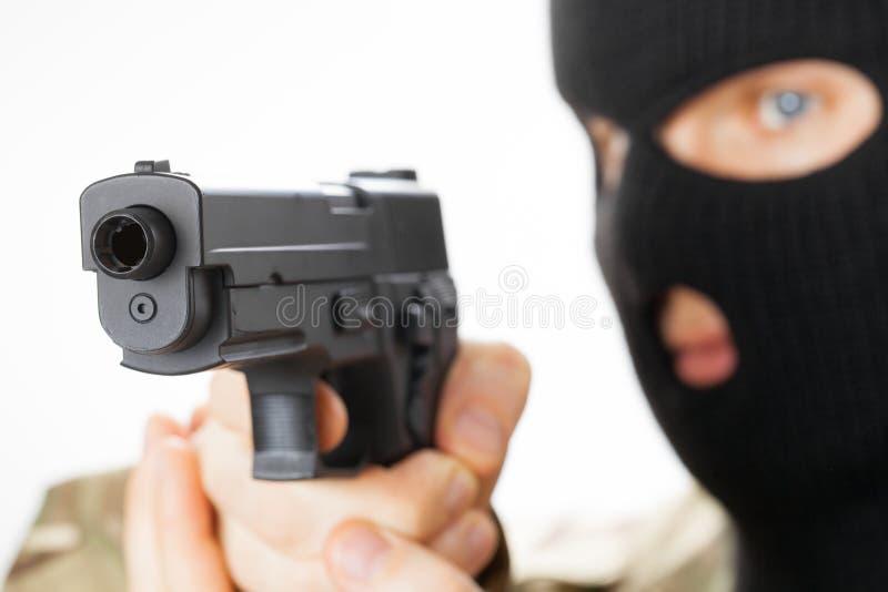 Uomo in pistola nera della tenuta della maschera davanti lui fotografia stock