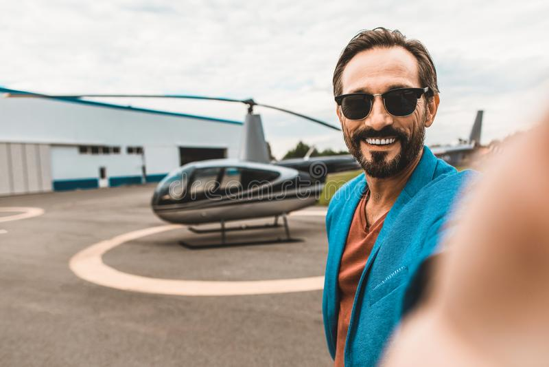 Uomo positivo che prende i selfies con l'elicottero e sorridere immagine stock