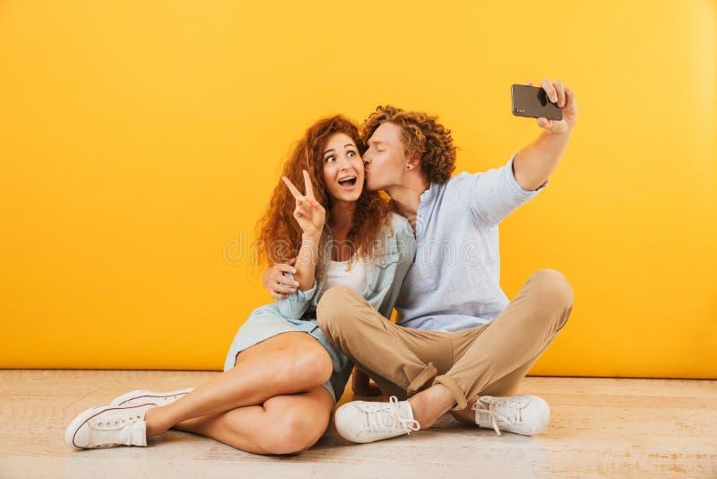 Uomo positivo della gente e donna svegli 20s che si siedono insieme sul pavimento immagini stock libere da diritti