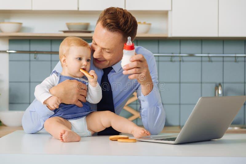 Uomo positivo felice che alimenta sua figlia immagine stock