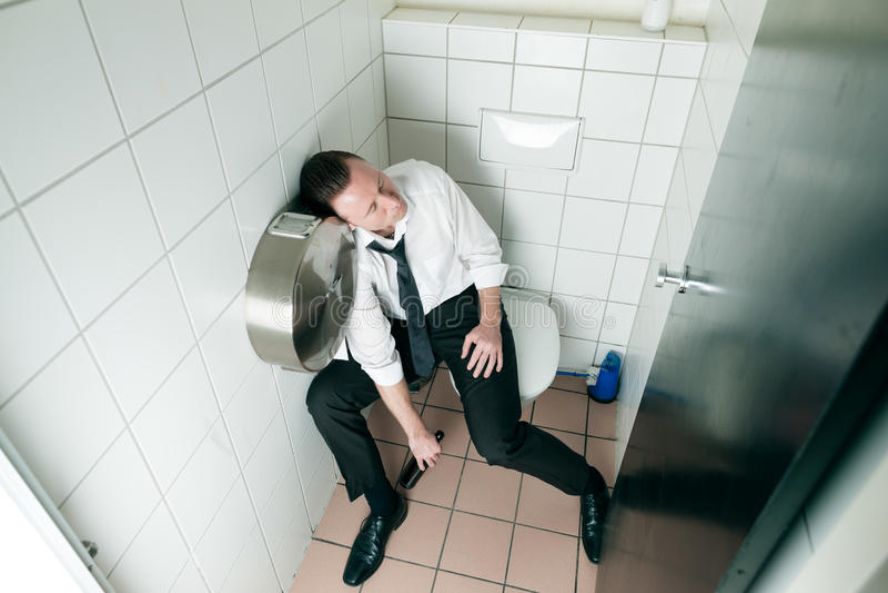 Uomo potabile addormentato dei giovani sul toilette immagine stock libera da diritti