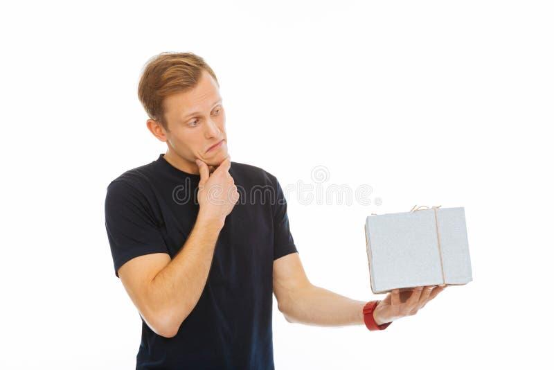 Uomo premuroso bello che esamina il suo presente immagine stock