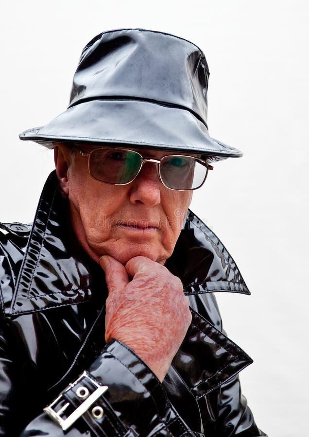 Uomo premuroso in cappotto e cappello neri fotografia stock