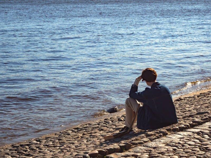 Uomo premuroso che si siede sulla riva immagini stock libere da diritti