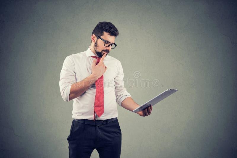 Uomo premuroso che tocca mento e che per mezzo del computer della compressa immagini stock