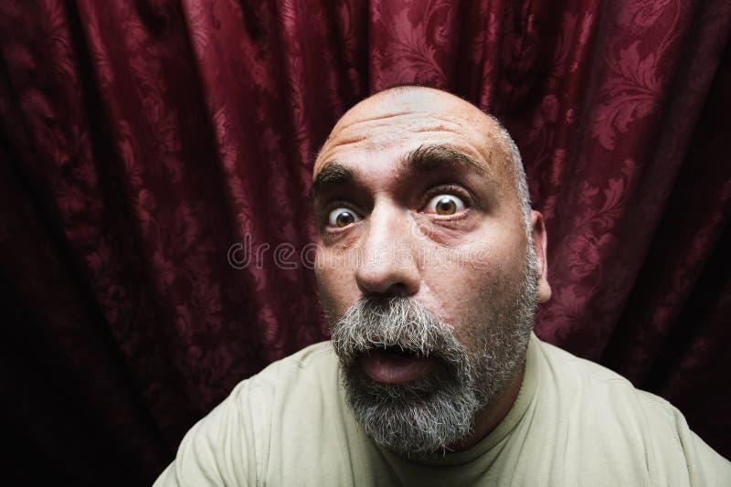 Uomo preoccupato davanti alle tende rosse fotografia stock