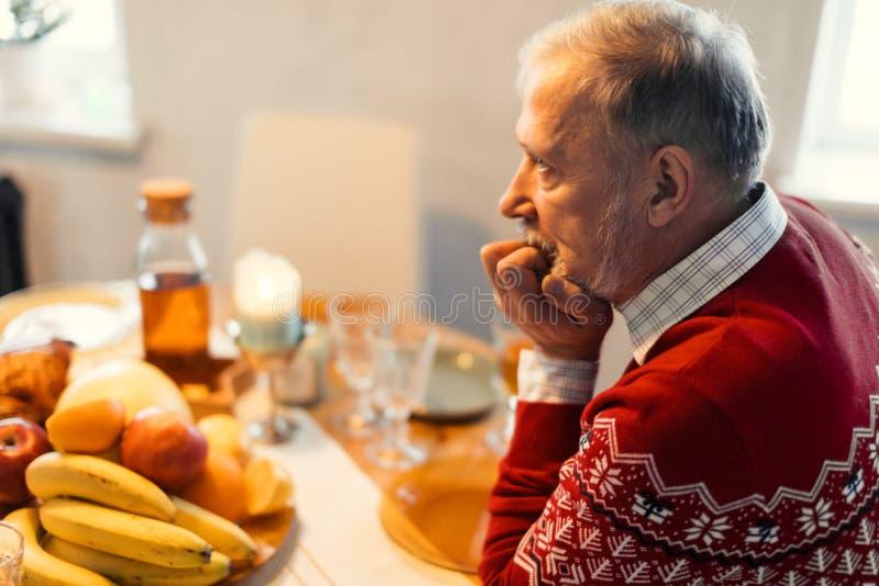 Uomo preoccupato depresso invecchiato che si siede da solo nella cucina fotografia stock libera da diritti