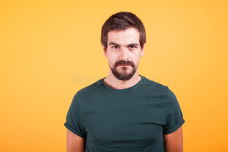 Uomo preoccupato sollecitato scontroso sul lookin giallo del fondo alla macchina fotografica fotografie stock libere da diritti