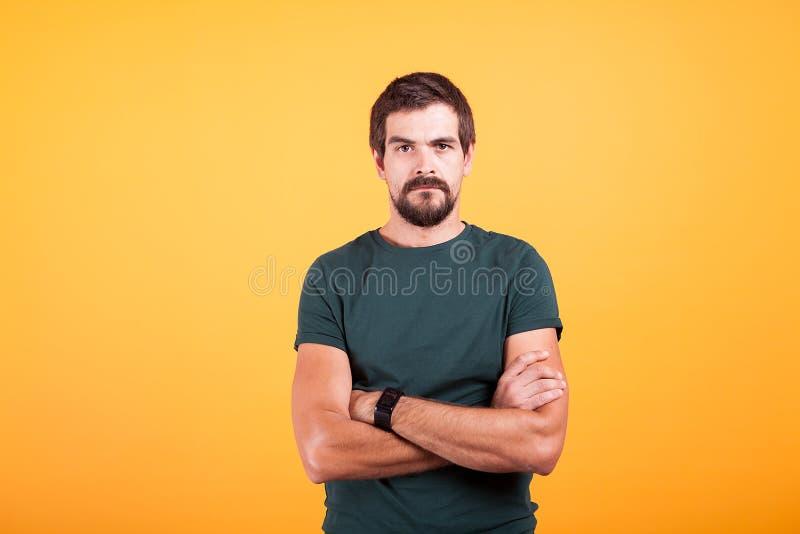 Uomo preoccupato sollecitato scontroso sul lookin giallo del fondo alla macchina fotografica fotografie stock