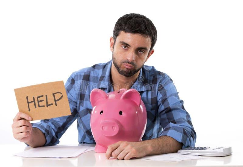 Uomo preoccupato triste nello sforzo con il porcellino salvadanaio nella cattiva situazione finanziaria fotografie stock libere da diritti