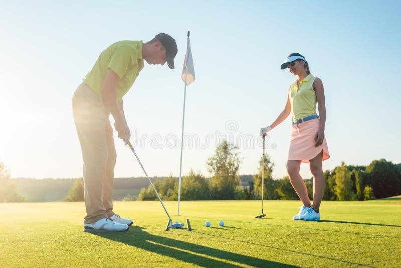 Uomo pronto a colpire la palla da golf mentre esercitandosi con il suo partner del gioco immagine stock libera da diritti