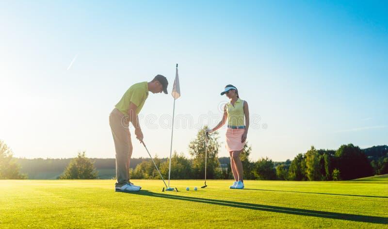 Uomo pronto a colpire la palla da golf mentre esercitandosi con il suo partner del gioco immagine stock