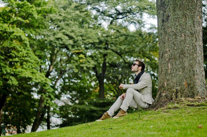 Uomo reale ben vestito restando sull'albero un vestito bianco immagini stock libere da diritti