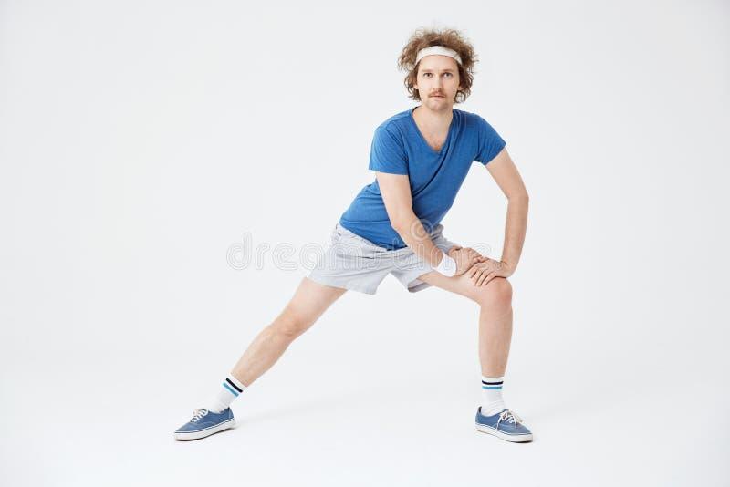 Uomo in retro abiti sportivi che si scaldano i muscoli prima del risolvere immagini stock libere da diritti