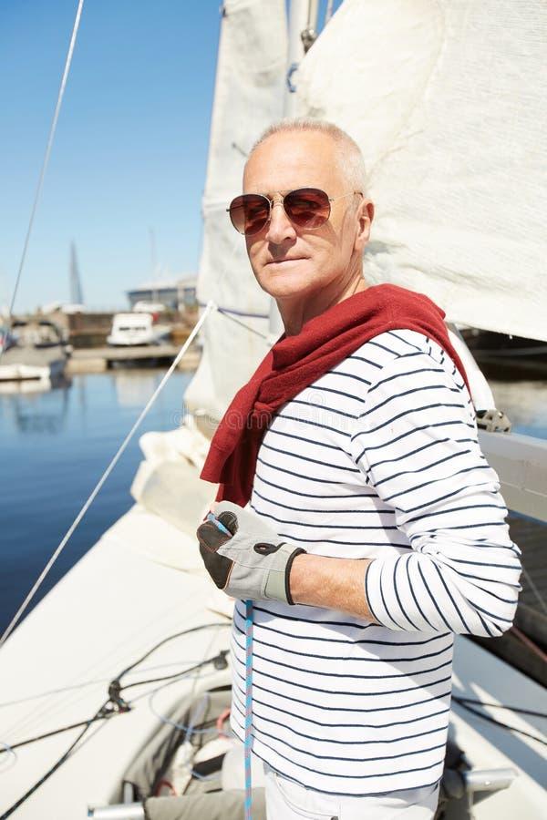 Uomo ricco al proprio yacht immagine stock
