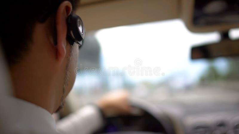 Uomo ricco occupato che conduce automobile al lavoro, traffico urbano, servizio del trasporto immagini stock