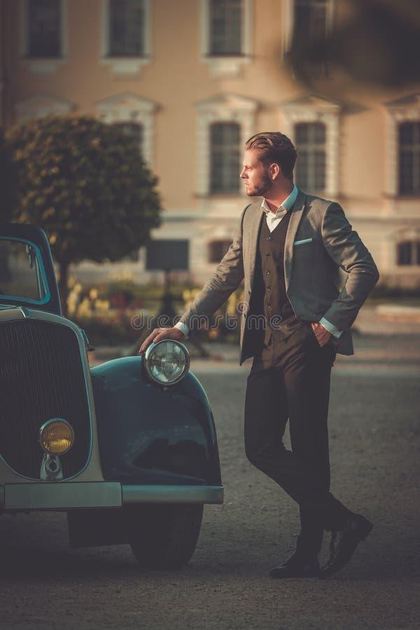 Uomo ricco sicuro con il giornale vicino al convertibile classico fotografie stock libere da diritti