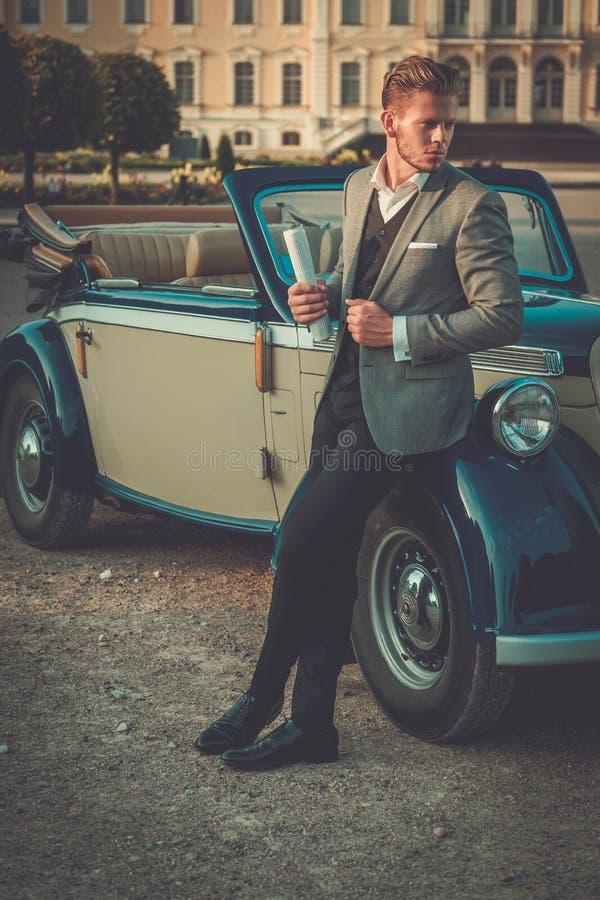 Uomo ricco sicuro con il giornale vicino al convertibile classico fotografia stock